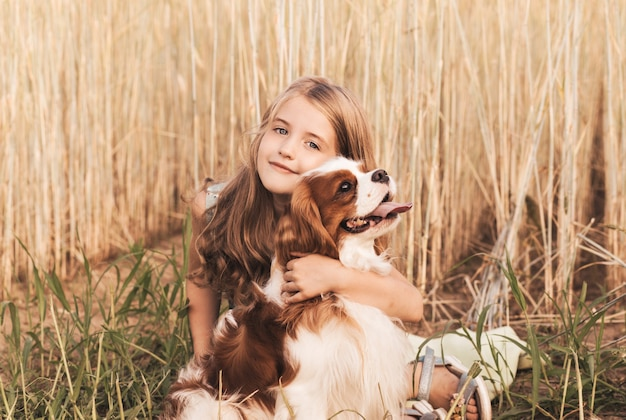 Kleines mädchen mit einem cavalier king charles spaniel hund, der im sommer in der natur spielt
