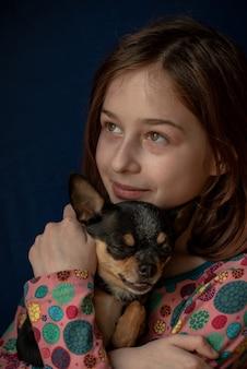 Kleines mädchen mit einem chihuahua. mädchen hält chihuahua. mädchen mit ihrem haustier in ihren armen. chihuahua in schwarz braun weißer farbe. kinder lieben ihre tiere. mädchen und chihuahua. kinder lieben ihre tiere