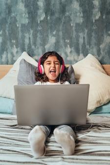 Kleines mädchen mit einem computer, der auf dem bett lacht