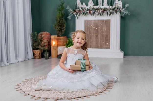 Kleines mädchen mit einem geschenk in ihren händen auf einem hintergrund vor dem hintergrund der weihnachtsdekoration.
