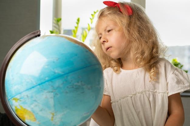 Kleines mädchen mit einem globus studiert geographie zurück zur schule