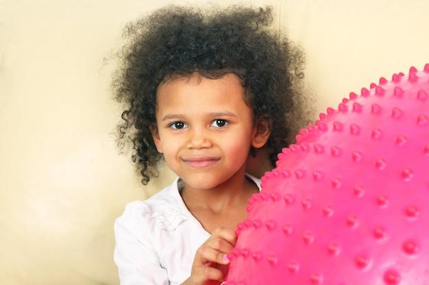 Kleines mädchen mit einem großen rosa ball