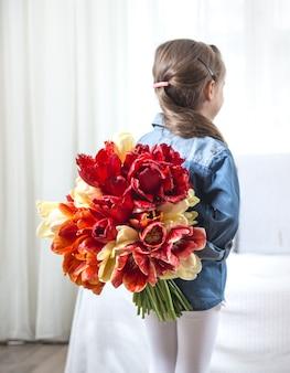 Kleines mädchen mit einem großen strauß tulpen