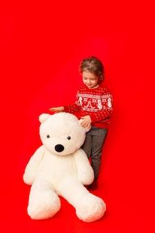 Kleines mädchen mit einem großen teddybär in der winterkleidung auf einem roten hintergrund, raum für text