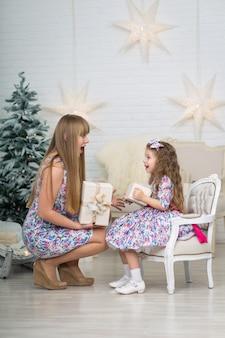 Kleines mädchen mit einem großen weihnachtsgeschenk zusammen mit mutter wirft nahe dem weihnachtsbaum auf