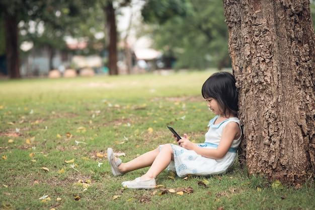 Kleines mädchen mit einem handy im park