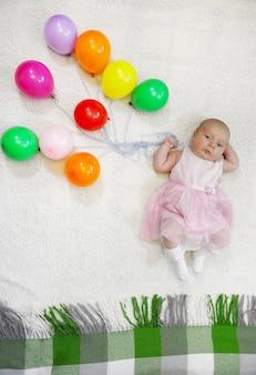 Kleines mädchen mit einem haufen luftballons und flugshows