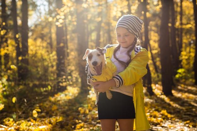 Kleines mädchen mit einem hundejack-russell-terrier im herbstpark