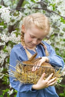 Kleines mädchen mit einem kaninchen im garten, frühling