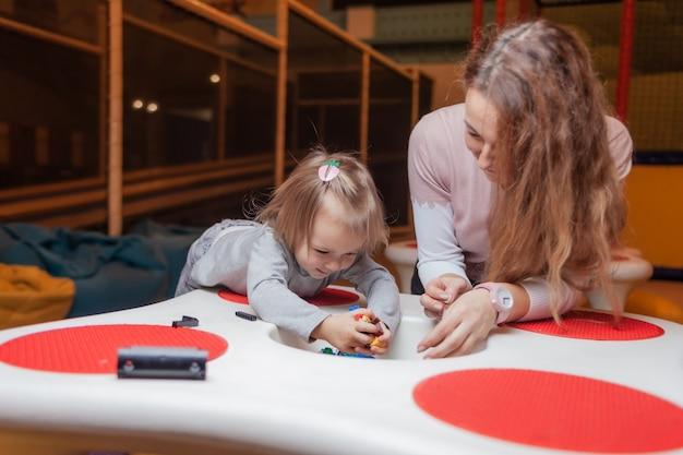 Kleines mädchen mit einem kindermädchen spielt spielzeugsteine am tisch in einem kinderunterhaltungszentrum