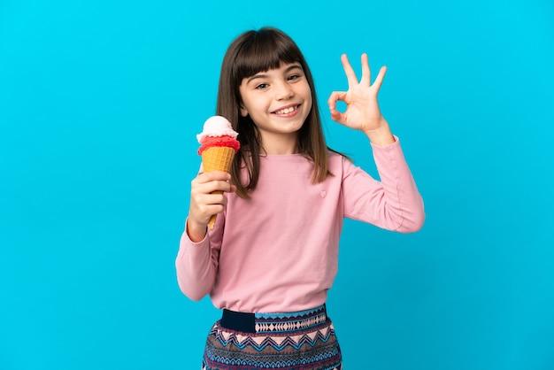 Kleines mädchen mit einem kornetteis lokalisiert auf blauer wand, die ok zeichen mit den fingern zeigt