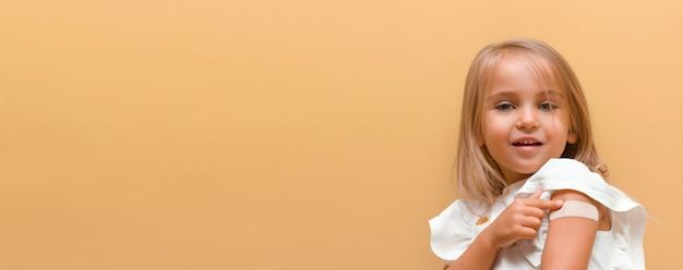 Kleines mädchen mit einem lächeln im gesicht, das die marke des impfstoffs auf gelbem hintergrund zeigt banner