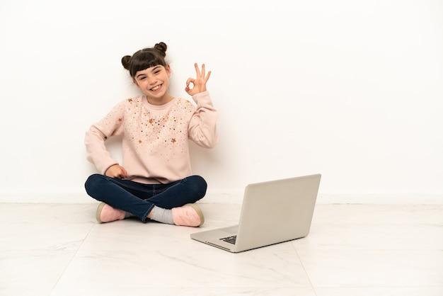 Kleines mädchen mit einem laptop, der auf dem boden sitzt und ein ok-zeichen mit den fingern zeigt