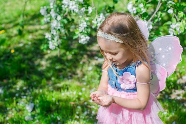 Kleines mädchen mit einem marienkäfer in den händen an blühendem apfelgarten