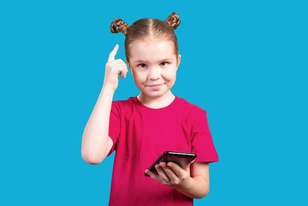 Kleines mädchen mit einem nachdenklichen gesichtsausdruck benutzt ein smartphone isoliert