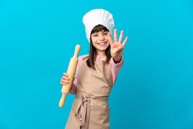 Kleines mädchen mit einem nudelholz isoliert auf blauem hintergrund glücklich und zählt vier mit den fingern