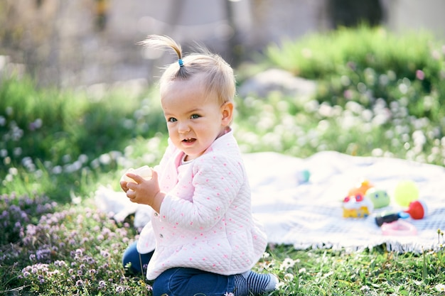 Kleines mädchen mit einem pferdeschwanz auf dem kopf sitzt auf einem grünen rasen zwischen den wildblumen und hält einen würfel