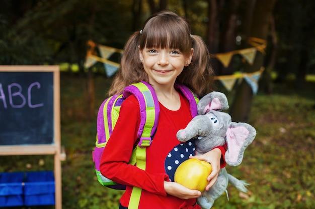 Kleines mädchen mit einem rucksack, einem apfel und einem elefanten. zurück zur schule. das konzept der bildung, der schule