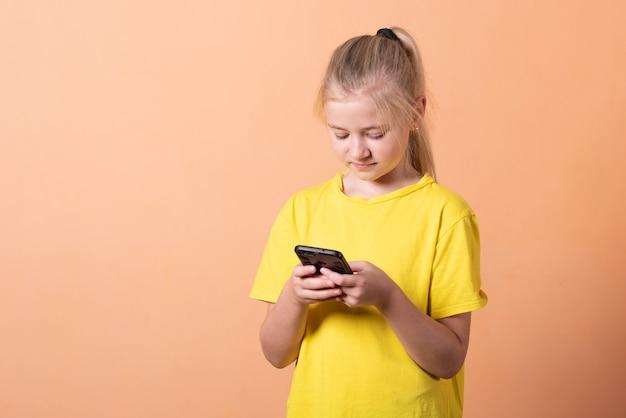 Kleines mädchen mit einem smartphone auf einem hellorangefarbenen hintergrund. für jeden zweck.