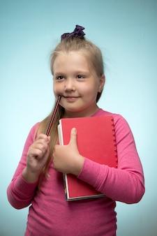 Kleines mädchen mit einem stapel bücher und einem bleistift in ihren händen an einer blauen wand. zurück zum schul- und bildungskonzept