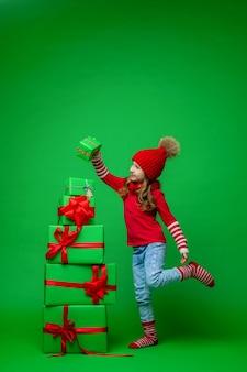 Kleines mädchen mit einem stapel weihnachtsgeschenkboxen