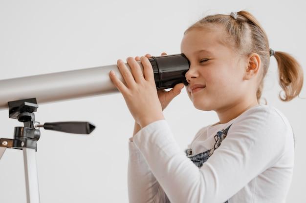 Kleines mädchen mit einem teleskop in der klasse