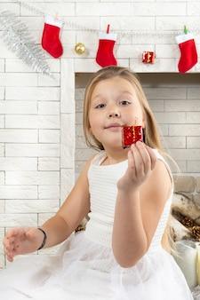 Kleines mädchen mit einem weihnachtsgeschenk