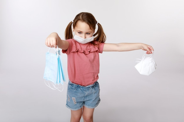 Kleines mädchen mit einer medizinischen maske auf ihrem gesicht, die viele medizinische und ffp2-masken hält