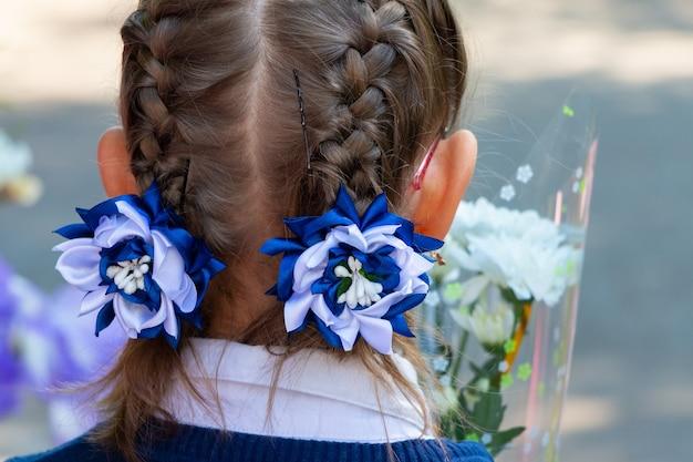 Kleines mädchen mit einer modischen frisur für die feiertage. mädchen mit zöpfen und eingewebten dekorativen blumen