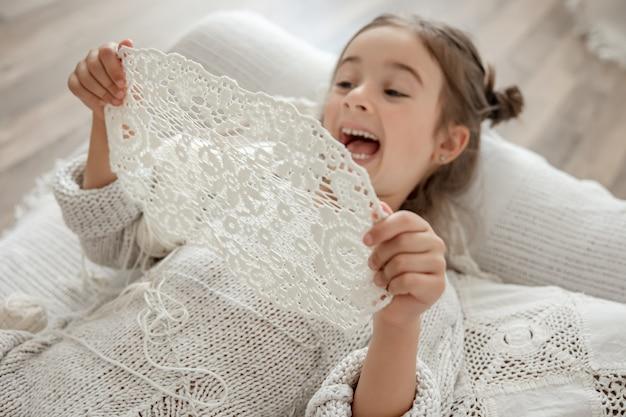 Kleines mädchen mit einer spitzenserviette aus natürlichem baumwollgarn, von hand gehäkelt. häkeln als hobby.