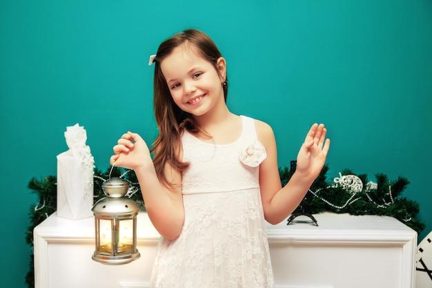 Kleines mädchen mit einer taschenlampe des neuen jahres. das neue jahr und frohe weihnachten