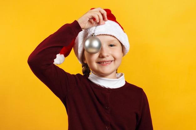 Kleines mädchen mit einer weihnachtskugel