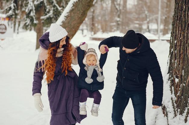 Kleines mädchen mit eltern in einem winterpark