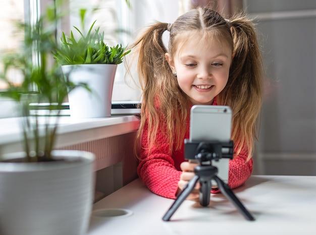 Kleines mädchen mit europäischem aussehen betrachtet das smartphone zu hause mit einem lächeln kommunikationskonzept
