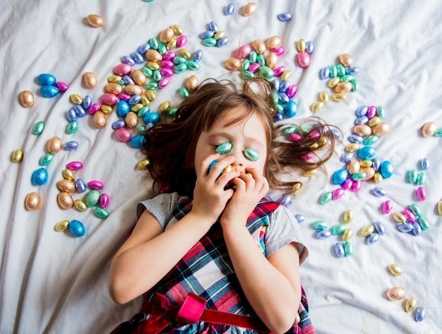 Kleines mädchen mit farbigen schokoladenostereiern in einem bett. ansicht von oben.