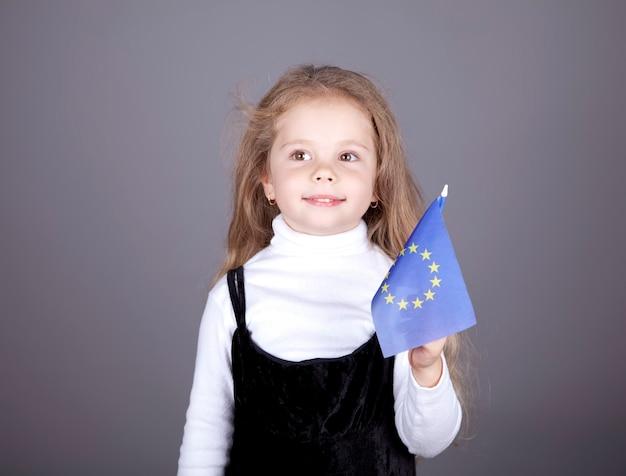 Kleines mädchen mit flagge der europäischen union.