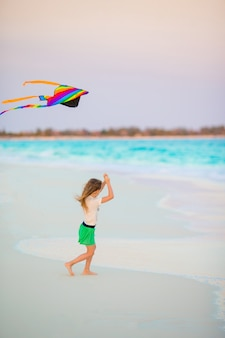 Kleines mädchen mit fliegenden drachen am tropischen strand. kinderspiel am ufer des ozeans. kind mit strandspielzeug.