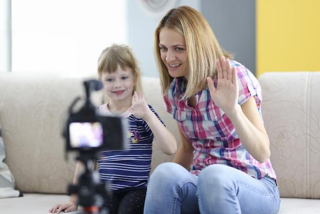 Kleines mädchen mit frau sitzt auf der couch und schaut in die kamera und hält dankbar ihre hand
