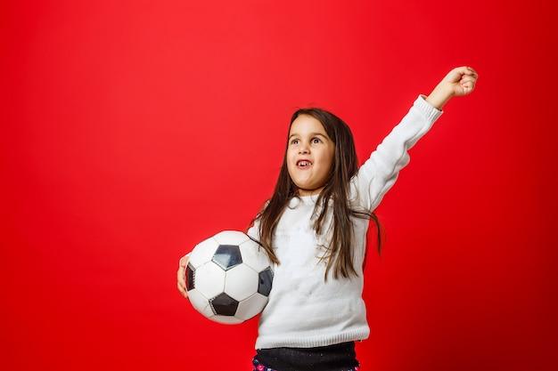 Kleines mädchen mit fußball auf rotem hintergrund