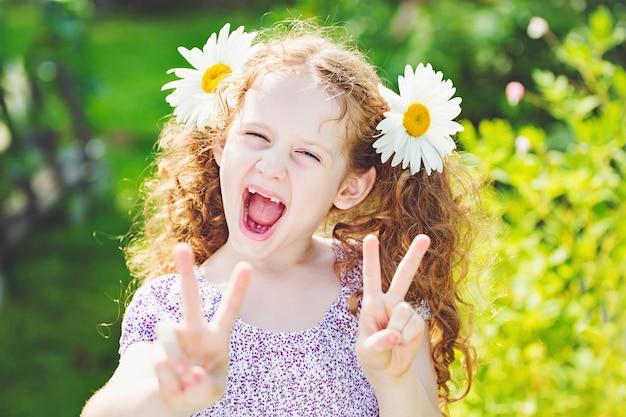 Kleines mädchen mit gänseblümchen in ihrem haar, das frieden oder sieghandtriumph zeigt.