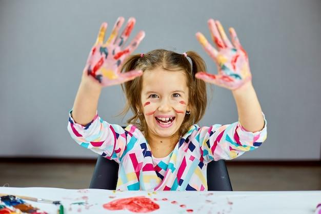 Kleines mädchen mit gemalten bunten aquarellhänden hoch, kind, das am tisch sitzt und zeichnet,