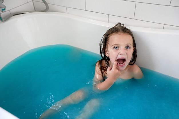 Kleines mädchen mit geöffnetem mund beim baden in der badewanne