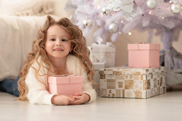 Kleines mädchen mit geschenk, geschenk unter dem weißen weihnachtsbaum.