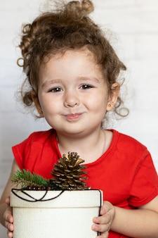 Kleines mädchen mit geschenk im paket von null abfall für weihnachten. glückliches kind mit geschenk für neues jahr in umweltfreundlichem zuhause.