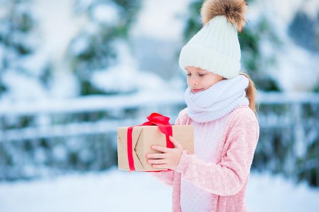 Kleines mädchen mit geschenk in gefrorenem wald am weihnachtsabend