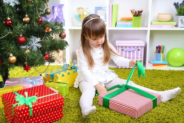Kleines mädchen mit geschenkbox in der nähe von weihnachtsbaum im zimmer