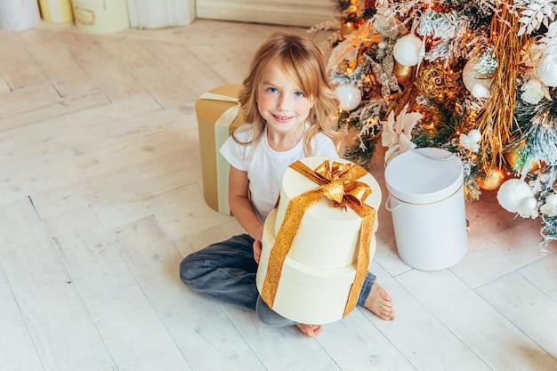 Kleines mädchen mit geschenkbox nahe weihnachtsbaum am weihnachtsabend zu hause. junge im hellen raum mit winterdekoration. weihnachtszeit für feierkonzept