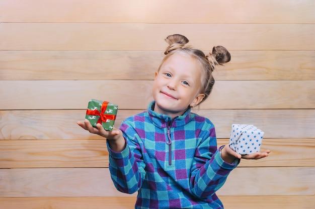 Kleines mädchen mit geschenken in den händen auf dem hintergrund der holzbretter.