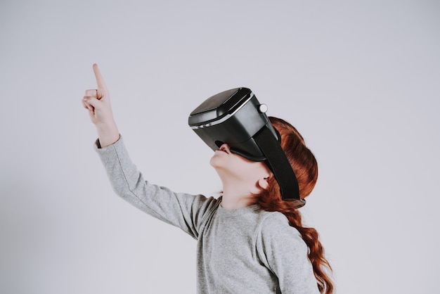 Kleines mädchen mit gläsern der virtuellen realität spielt spiel