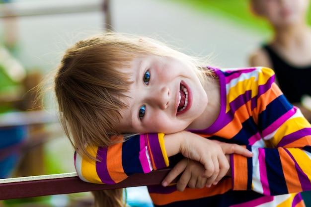 Kleines mädchen mit glücklichem ausdruck auf ihrem gesicht, das draußen spielt